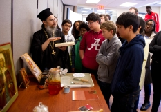 A local orthodox monk and iconographer teaches Middle School students about how to paint an icon