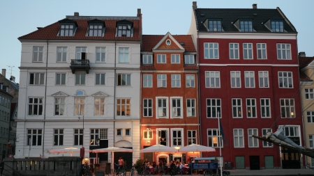Three close Danish apartments with unique angles on roofs during early evening near harbor in Copenhagen